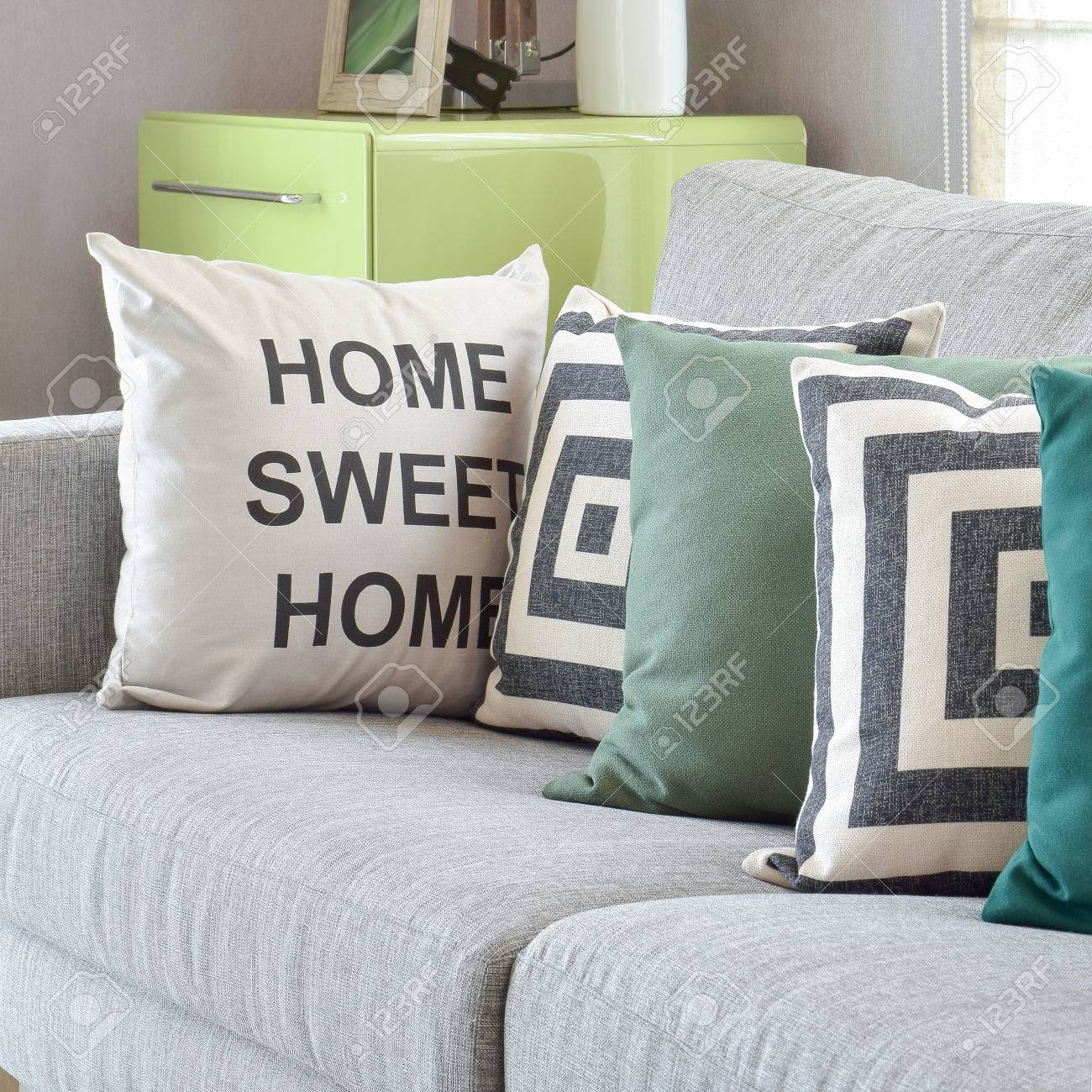 Canapé gris confortable avec des oreillers de modèle de géométrie dans le  salon moderne