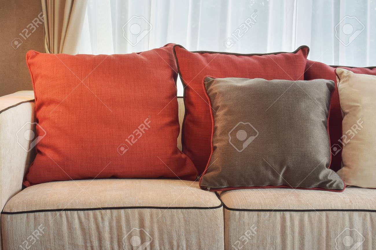 Red and deep brown linen pillows on beige linen sofa in modern classic living room stock