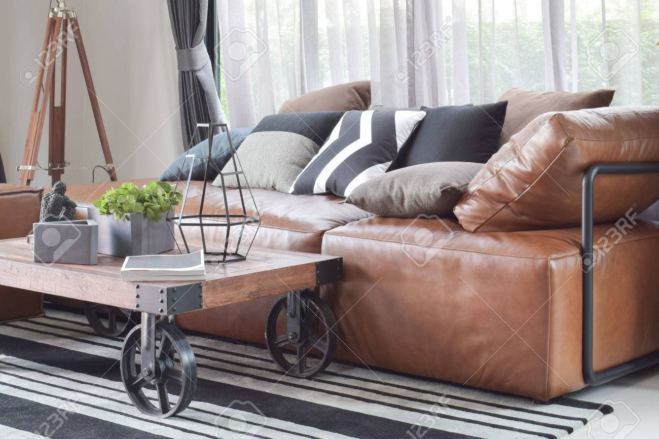 Wood center table with wheel and light brown leather sofa in..