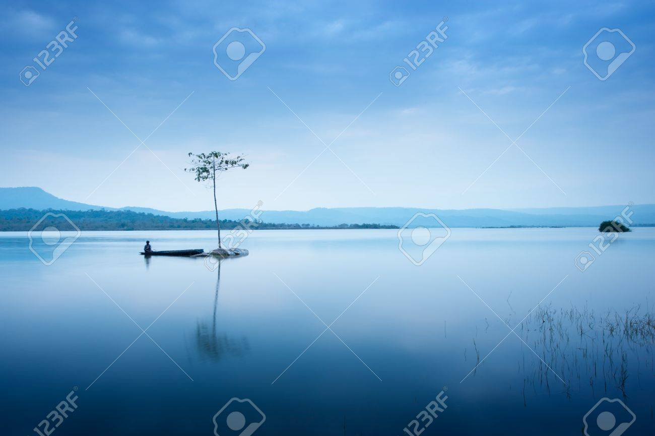 Fisherman in  fishing boat at big lake on the mountain Stock Photo - 8861850