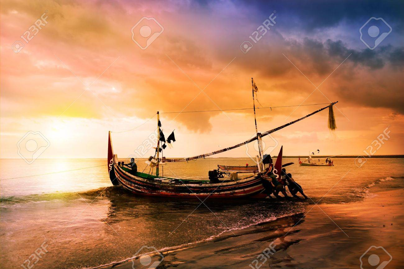 local boat on the beach at sunset time . bali , indonesia stock