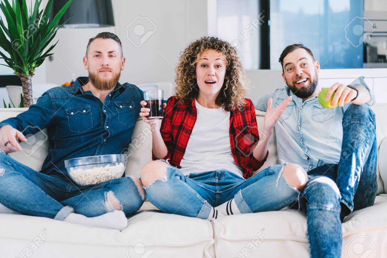 Three friends spending their day-off in front of the tv sitting..
