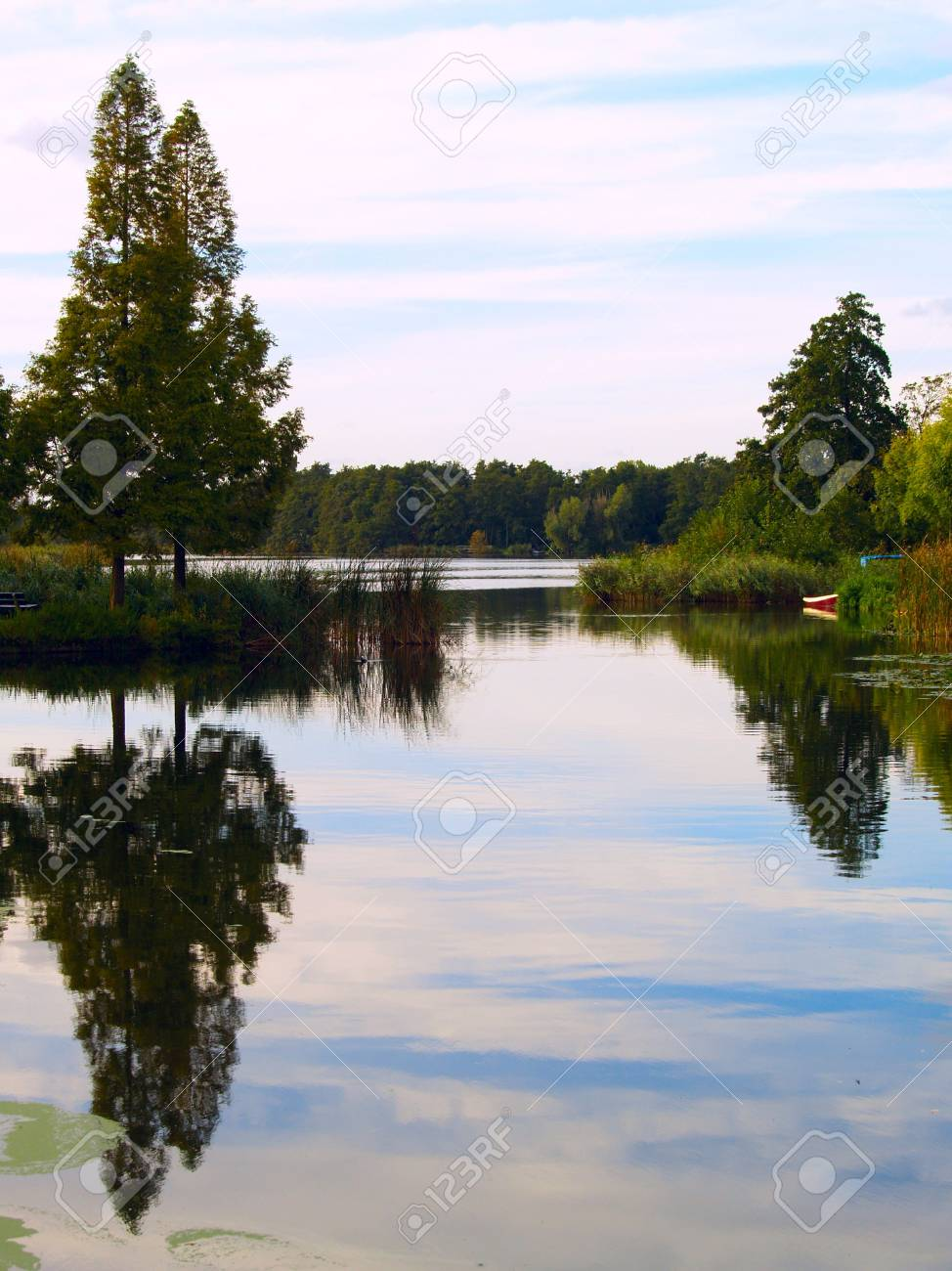 Landscape with reflecting trees and a little red boat Stock Photo - 2413442