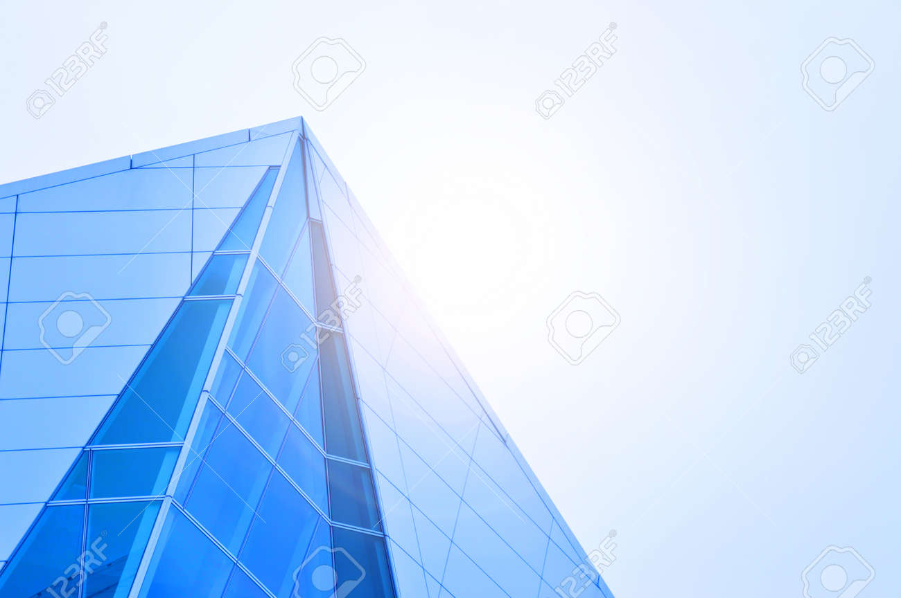 Side view of Skyscraper Business Office with blue sky, Corporate building in city with light flair. - 139814755