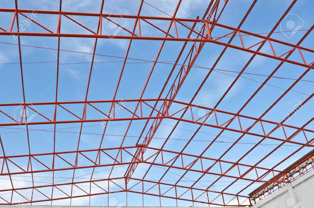 steel roof trusses sitting on concrete pole view from inside home factory blue sky with