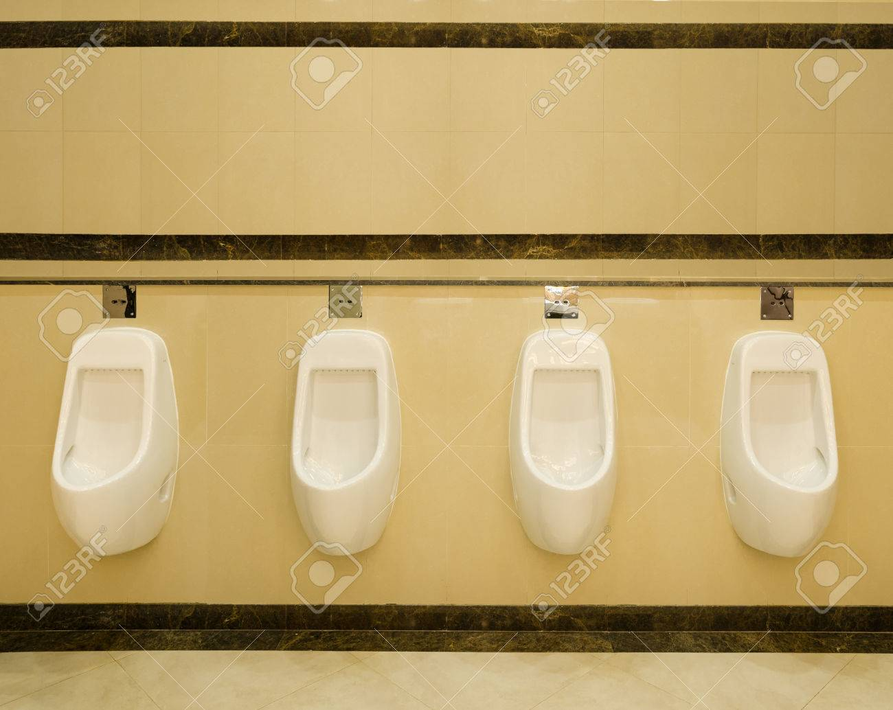 L\'intérieur des toilettes décoration de style moderne avec du blanc rangée  urinoir.
