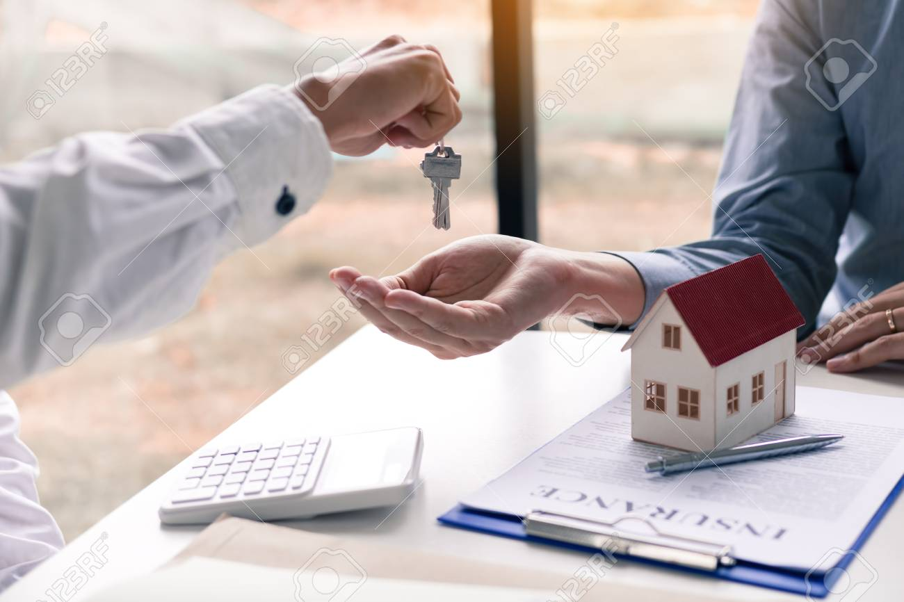 Salesman house brokers provide key to new homeowners in office. - 115913680