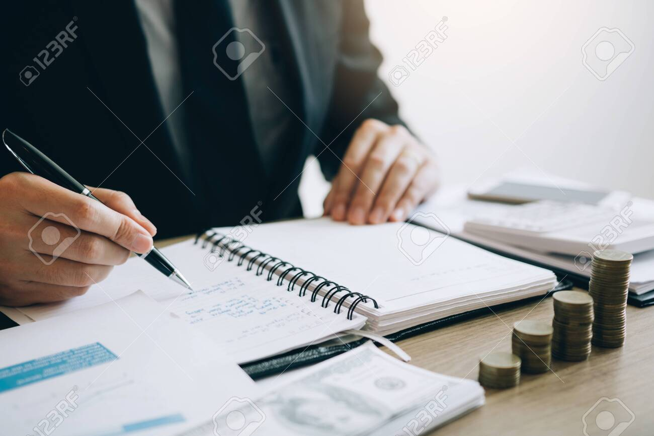 Businessmen are calculating the cost of the company's sales and analyzing the graph in the office. - 120428389