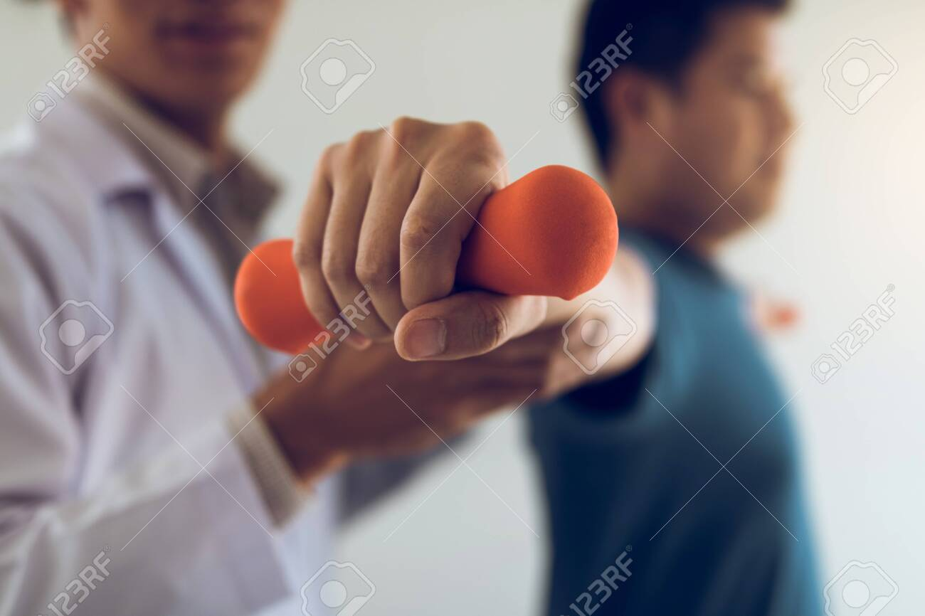 Asian young male physiotherapist helping patient with lifting dumbbells exercises in office. - 123934610