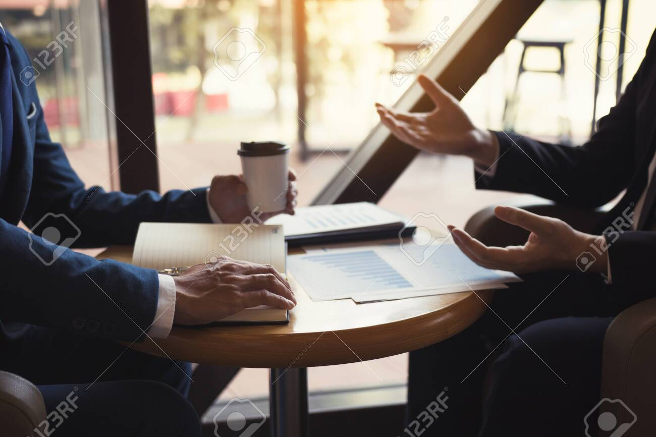 Two business partnership coworkers analysis cost work progress and gesturing with discussing a financial planning graph and company financial during a budget meeting in office room. - 127029474