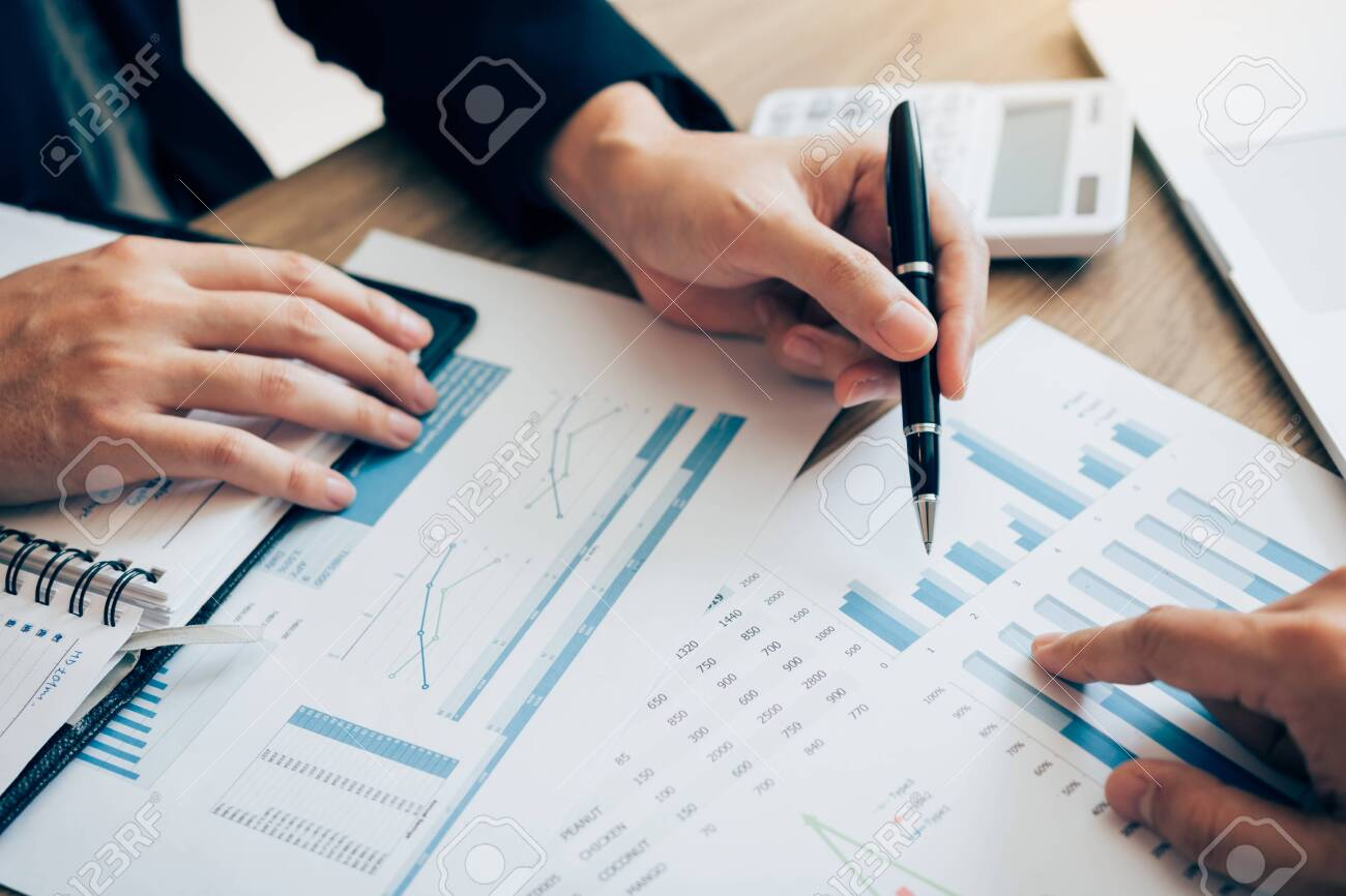 The accounting staff of the company are jointly analyzing the graph of the expenses on the desk in the office. - 128508986