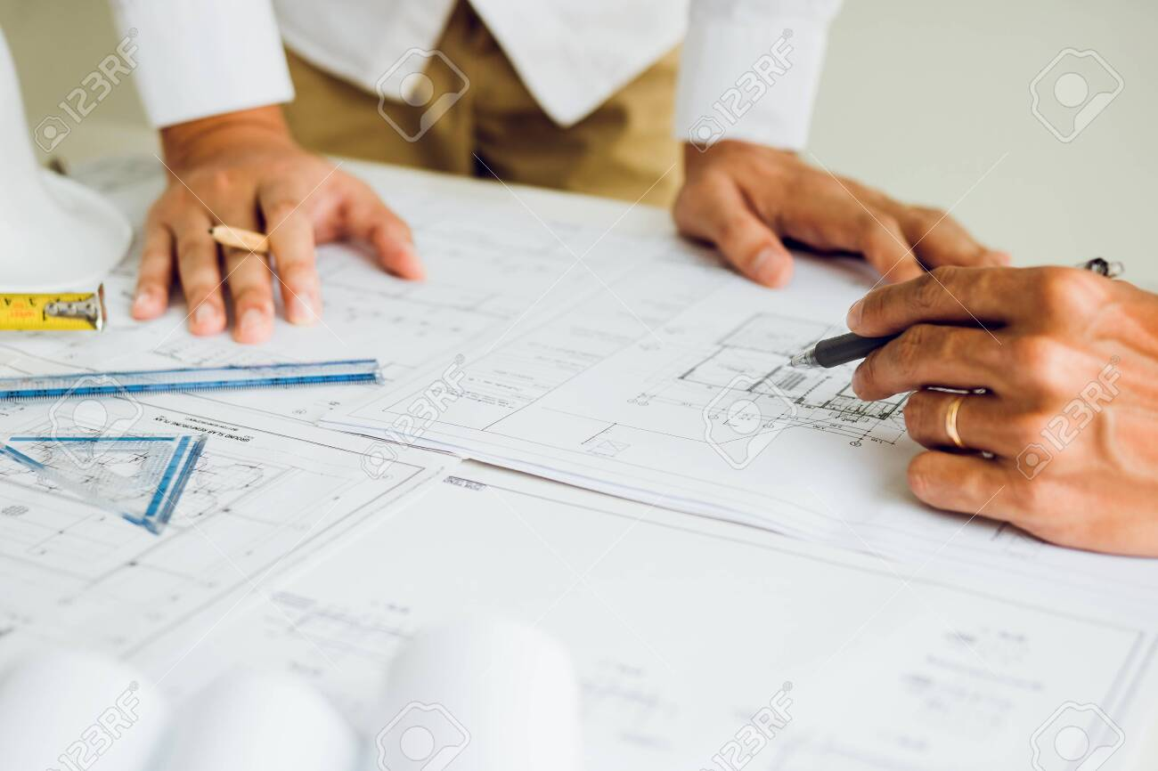 Two partnership architects or engineering working with blueprints and discussing project together at the meeting in the office. - 148497697