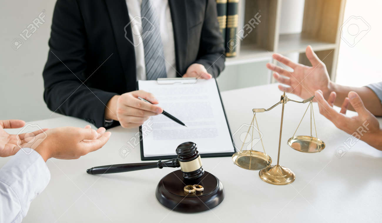 Couples are arguing in a poignant mood in the divorce process while the lawyer is explaining the law at the office. - 156067258
