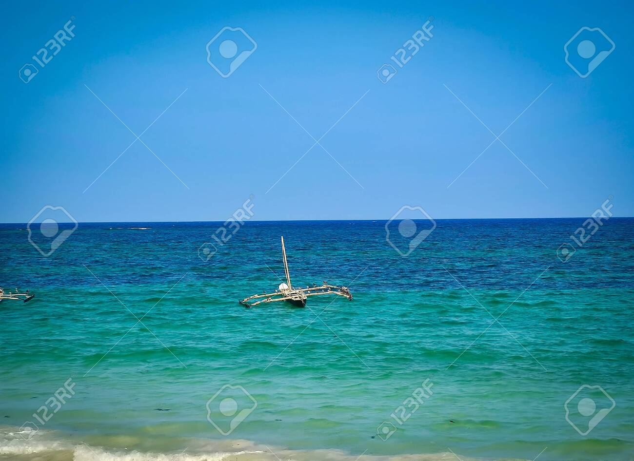 Typical Swahili wooden canoe on the sea at Diani beach, Kenya. It is a beautiful long beach in Africa. It is a sunny day. - 145110065