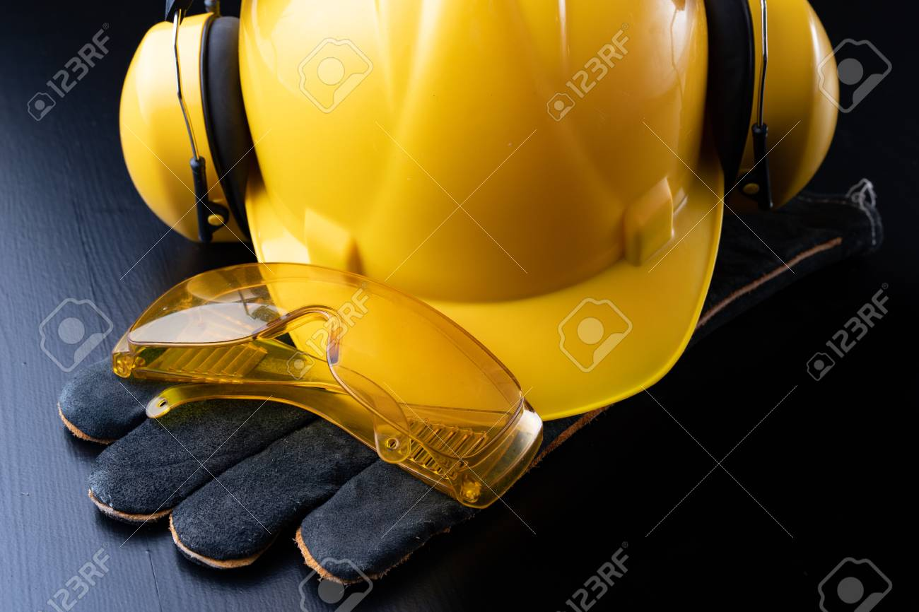 Helmet and accessories for construction workers. Accessories needed for work on the construction site. Dark background. - 116559840
