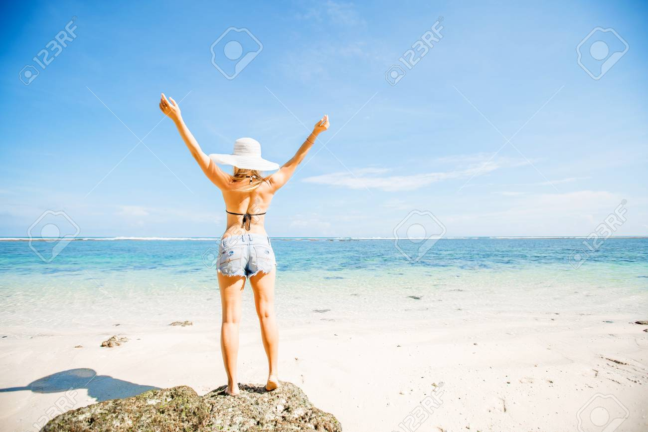 young skinny caucasian girl with tan stays on the rock facing