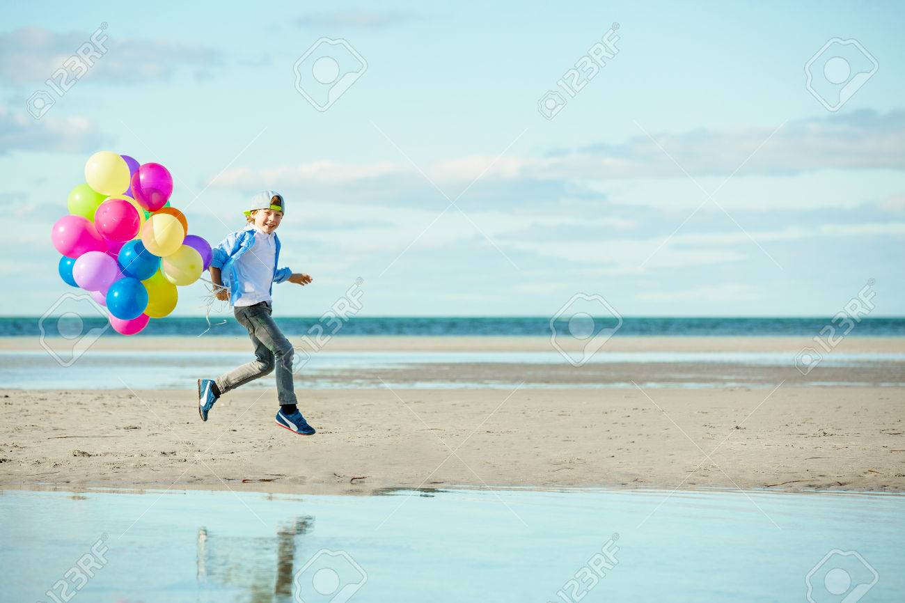 Happy Boy Plays With Colored Balloons On The Beach Having Great Holidays Time On Summer