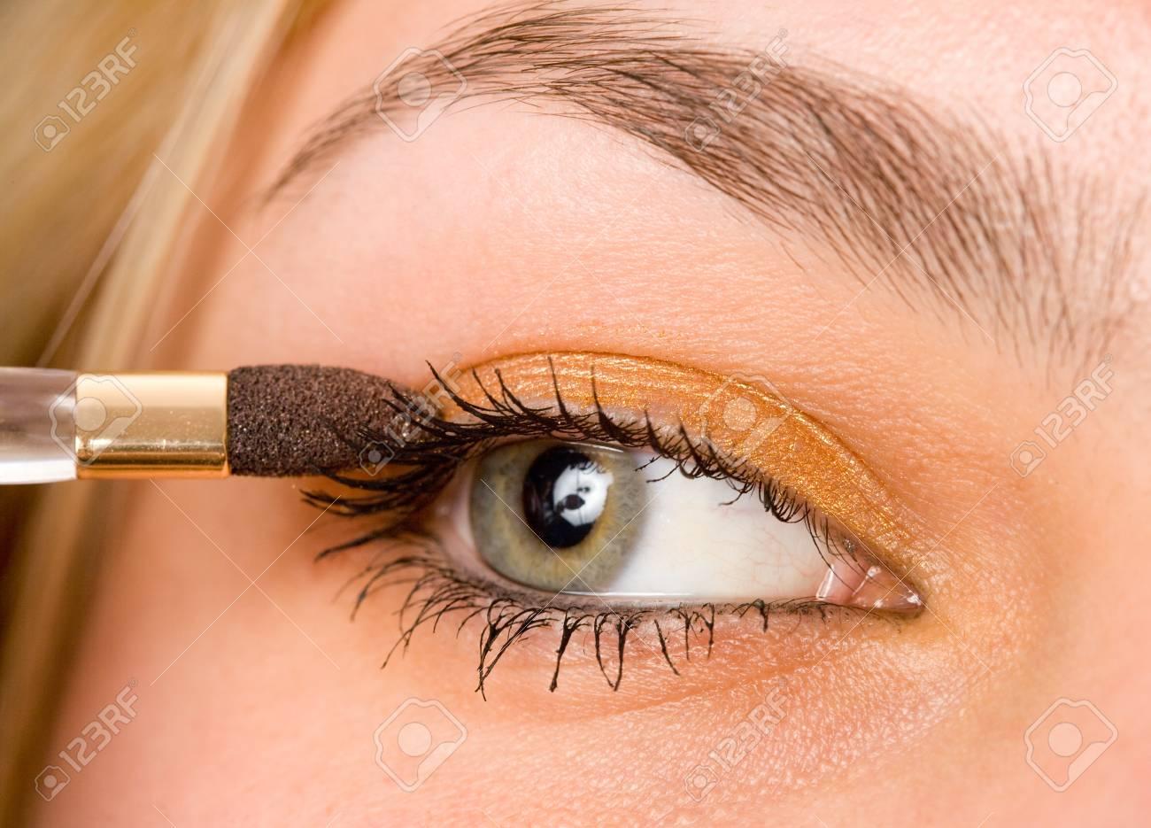 Closeup portrait of a beautiful woman applying makeup Stock Photo - 4419519
