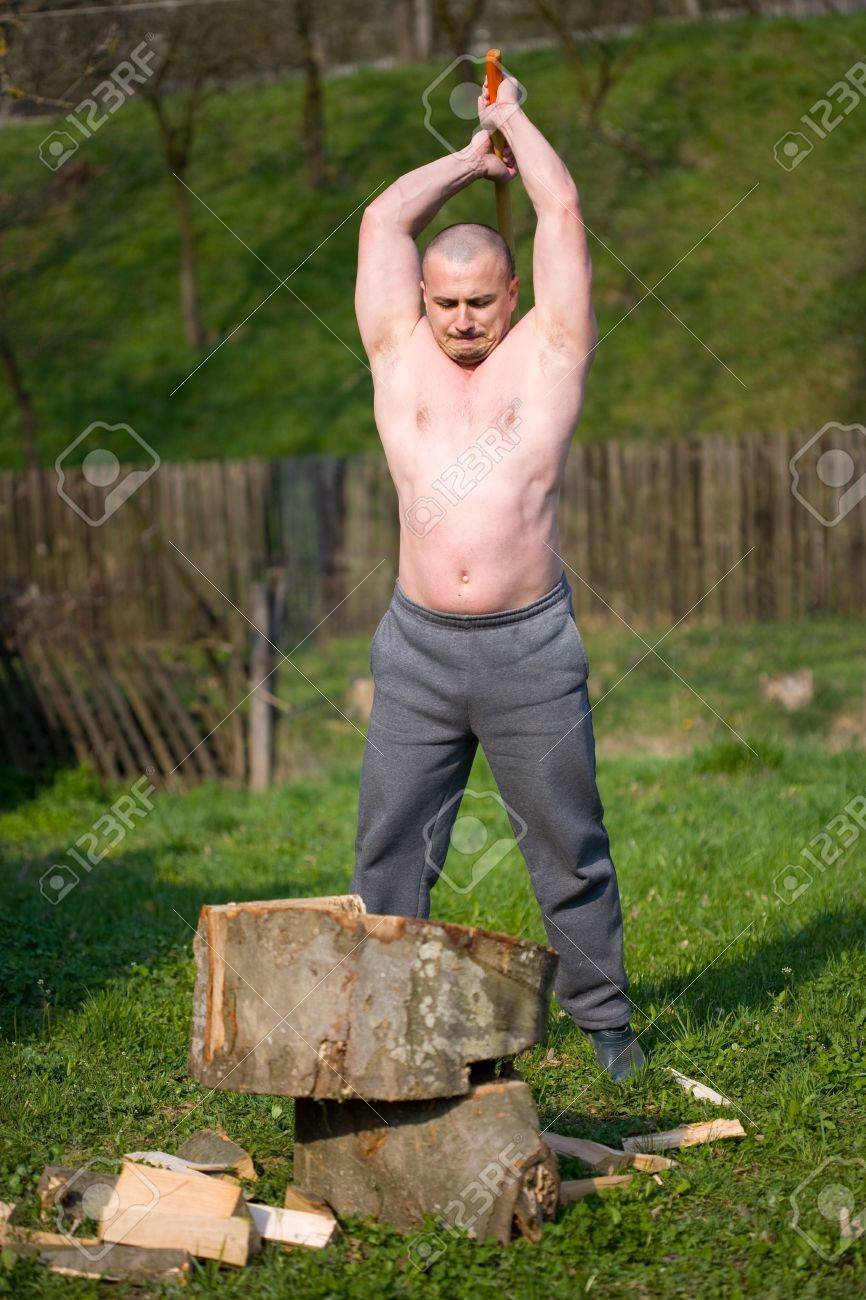 Strong man splitting wood with an axe in the countryside Stock Photo - 4761228