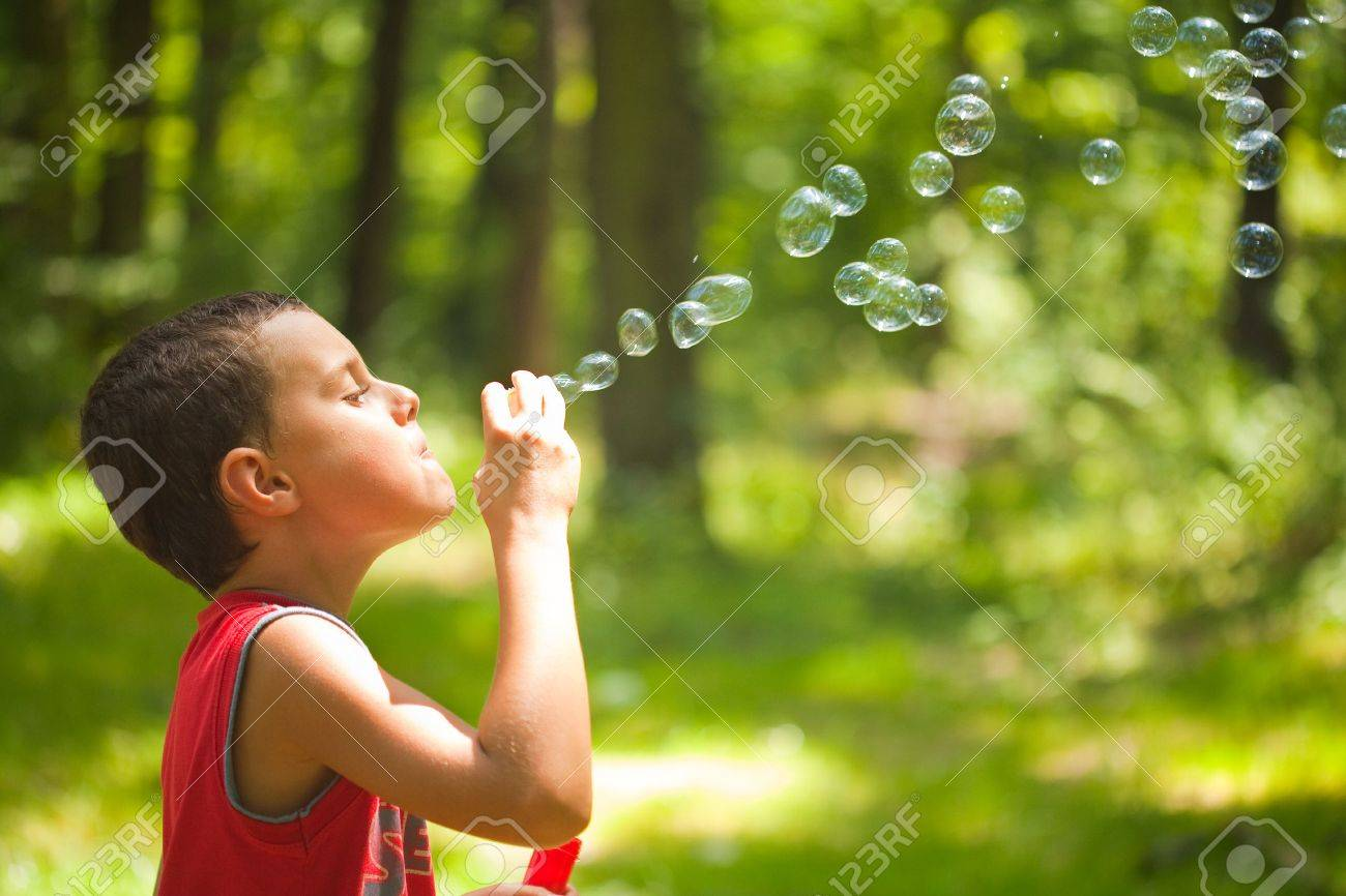 cute kid blowing bubbles outdoors, in the forest in a beautiful