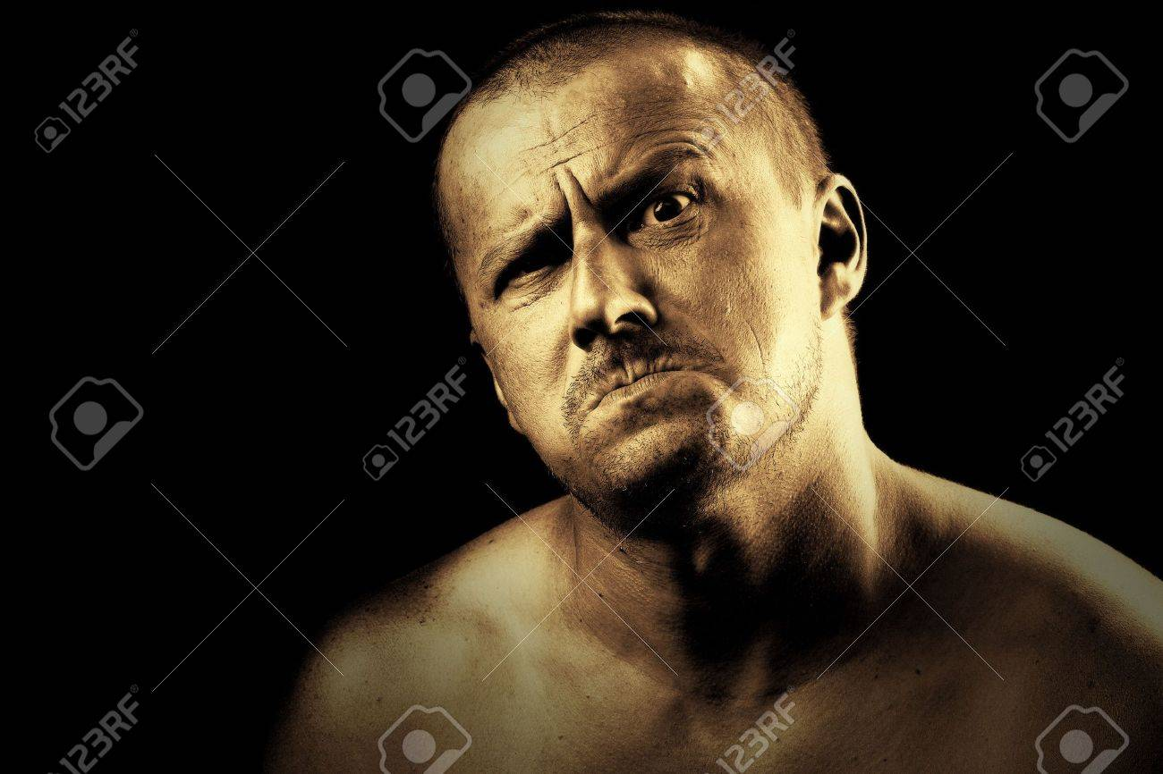 Low key portrait of a dangerous angry strong man with a scary expression Stock Photo - 5318284