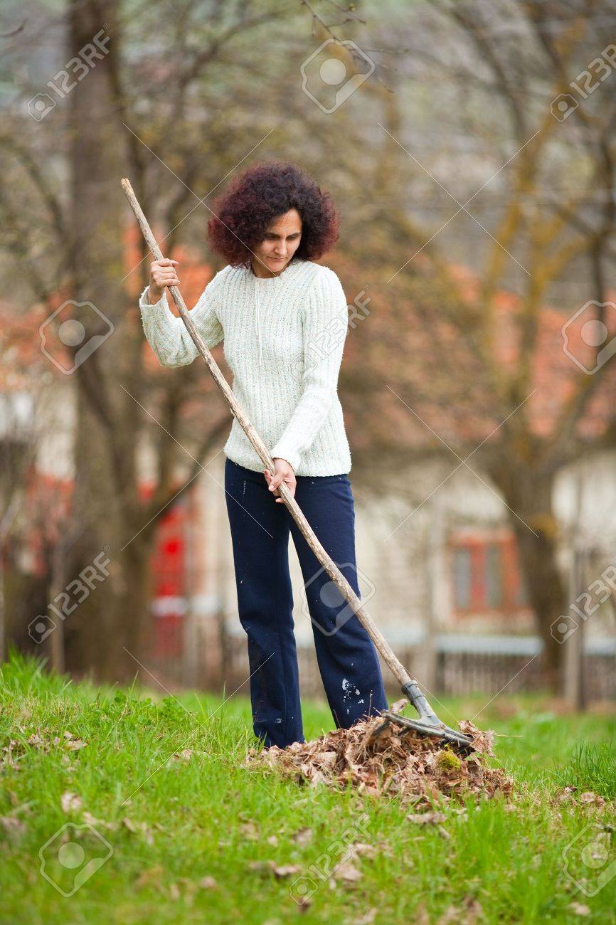 Young redhead pretty country girl using a rake to clean up of the fallen leaves Stock Photo - 6792650