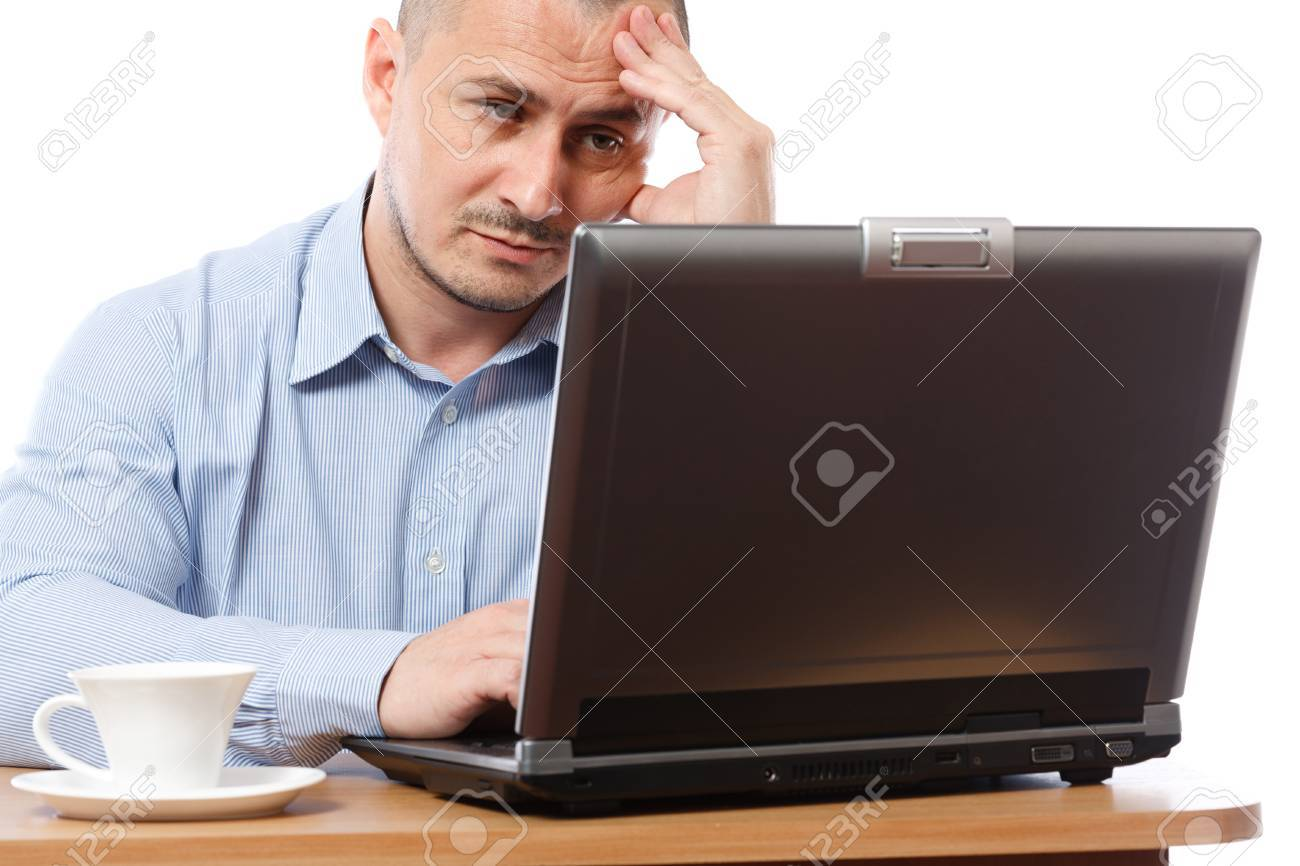 Tired and stressed young businessman working at his computer Stock Photo - 8395934