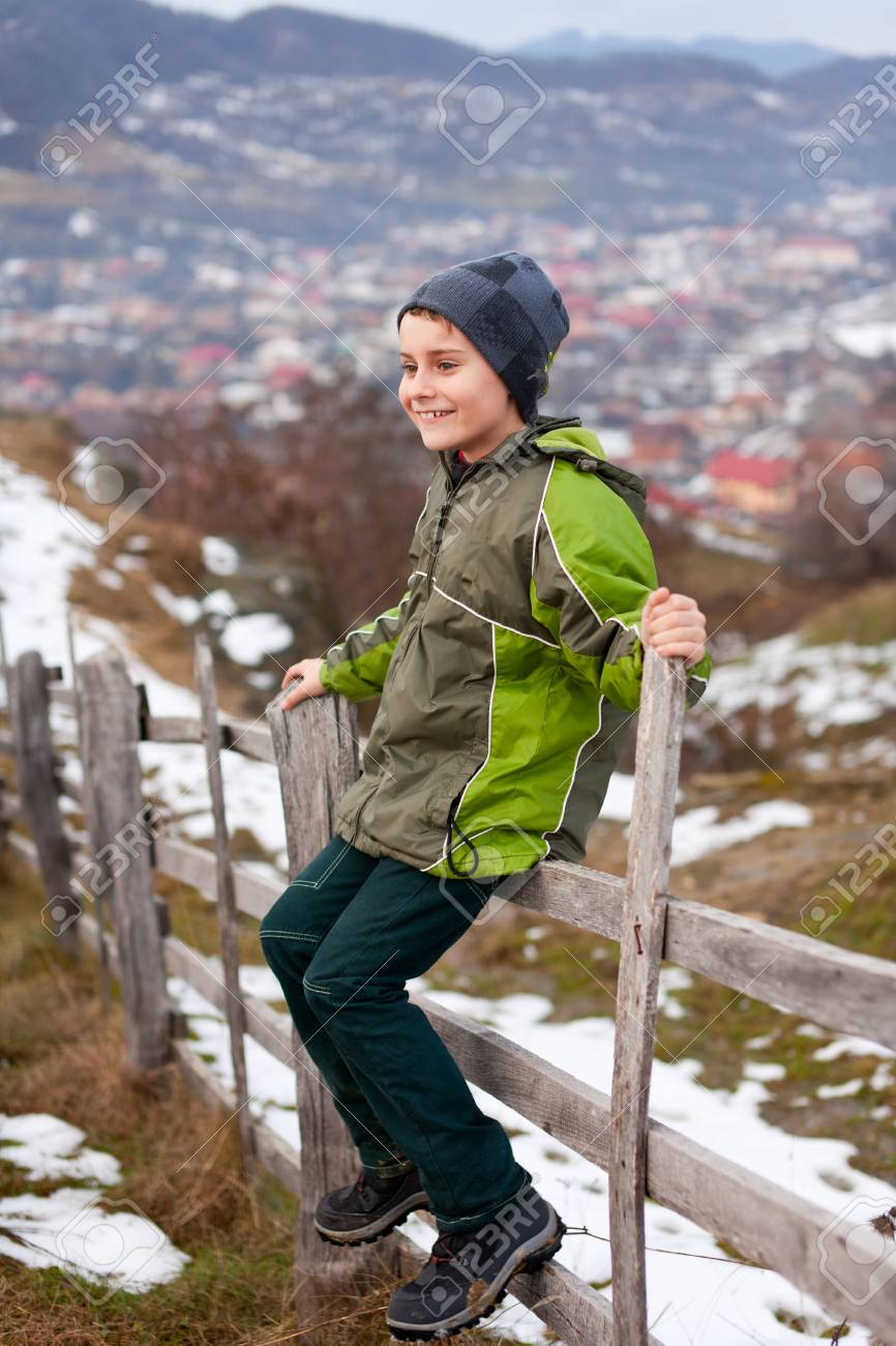 Little boy sitting on a wooden fence in the countryside Stock Photo - 8553582