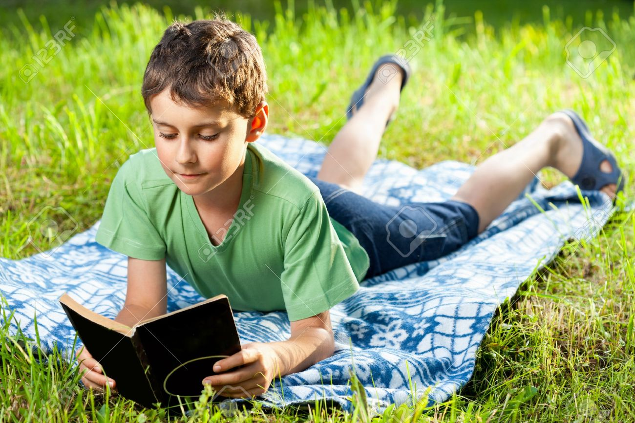 Portrait of a boy reading a book outdoor on the grass Stock Photo - 9849564