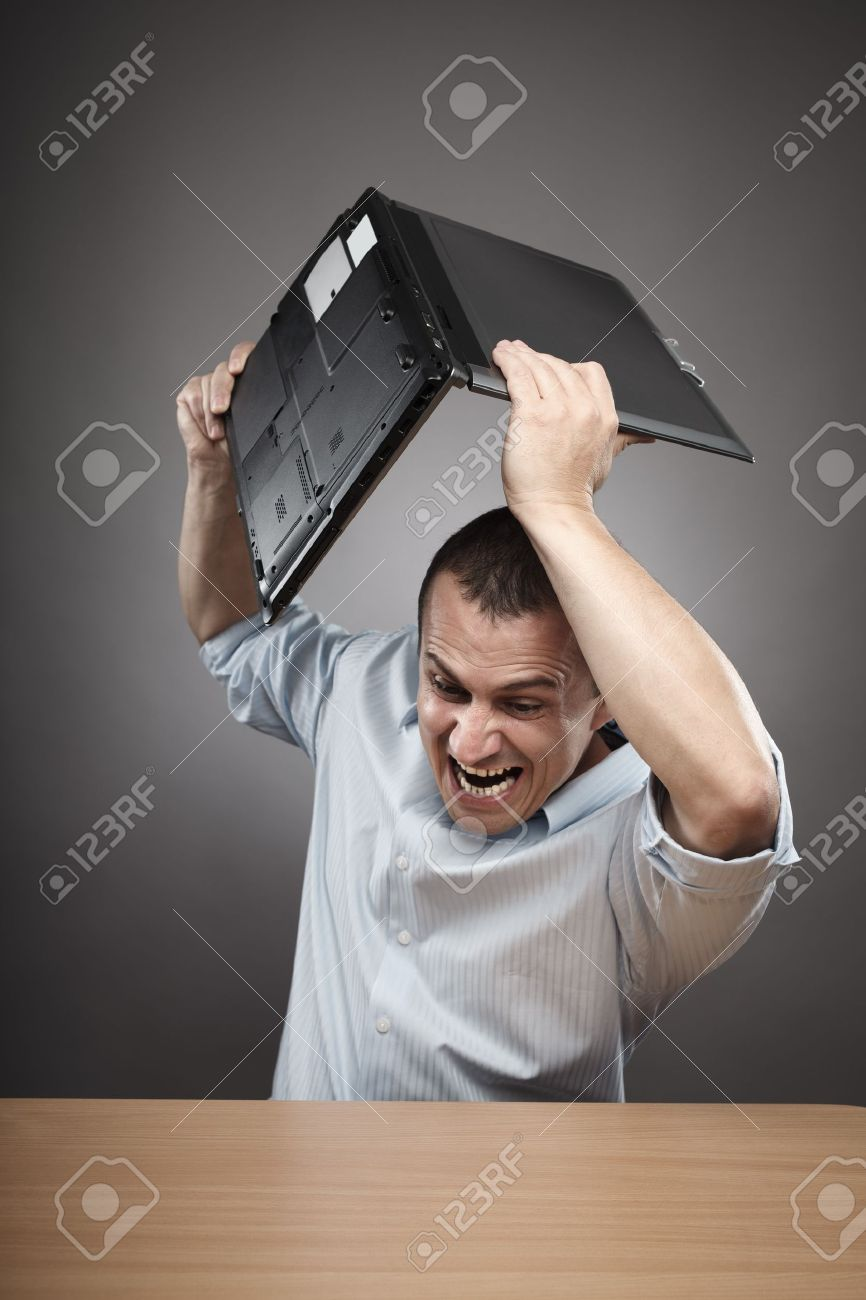 Extremely angry businessman smashing his laptop on the desk Stock Photo - 10497026