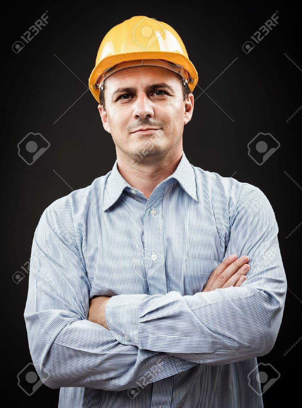 Young construction worker in hard hat on gray background Stock Photo - 15662324