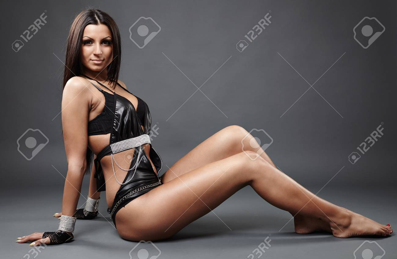 Close-up profile of hot exotic dancer in leather lingerie sitting on the  ground,