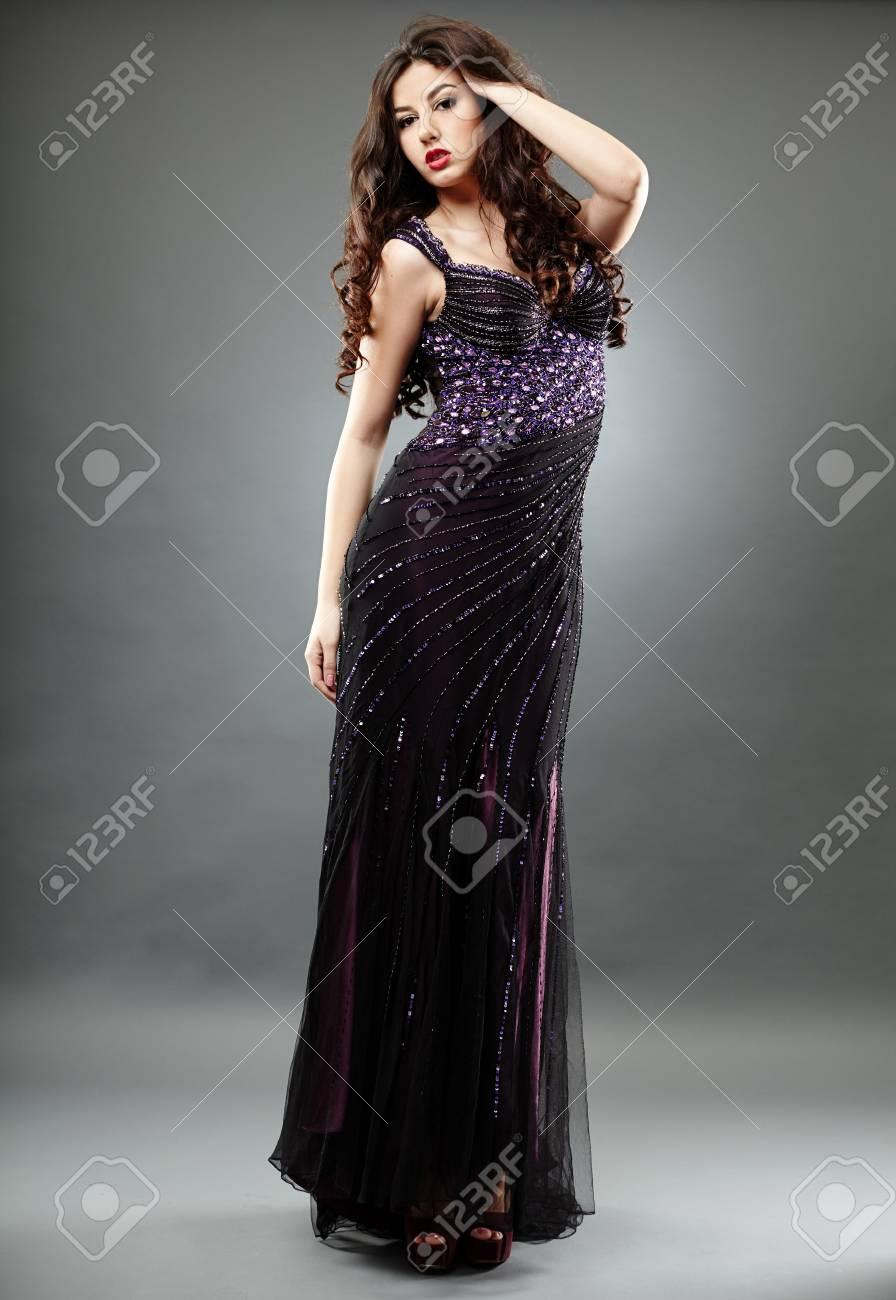 Young brunette model in elegant long dress, on gray background in full length pose Stock Photo - 18062012