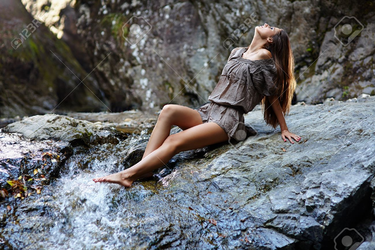 MUJER !!!!!  - Página 19 22355916-sexy-young-woman-laying-on-the-mountain-rock-near-a-waterfall