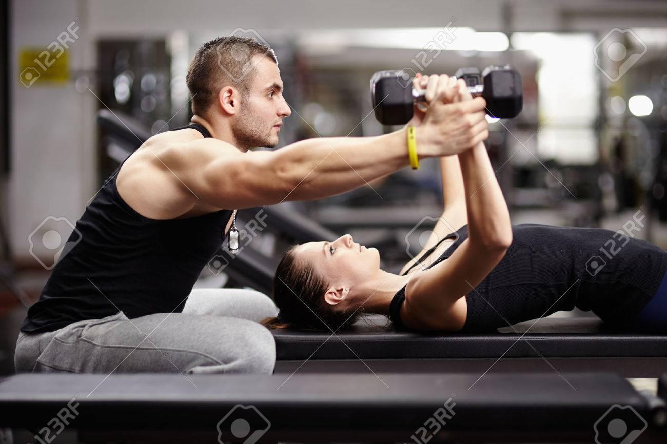 Personal trainer aidant femme travaillant avec des haltères lourds Banque d'images - 24712142