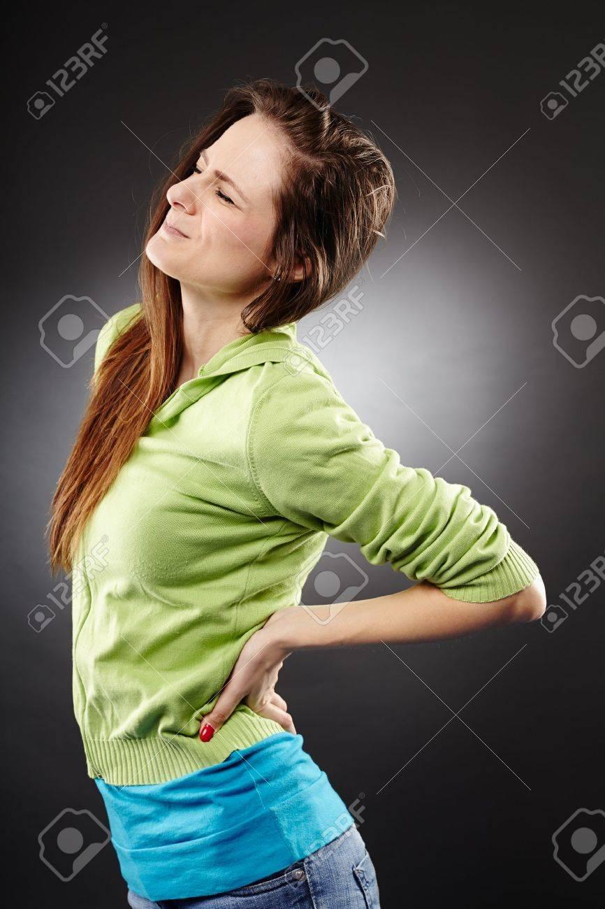 Studio photo d'une jeune femme ayant une douleur lombaire sévère sur fond gris Banque d'images - 25084285