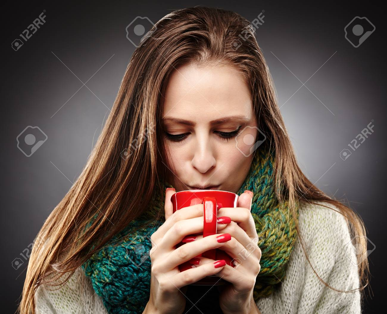 Closeup of  a woman with flu wrapped up in a scarf and drinking hot tea over gray background Stock Photo - 25084288