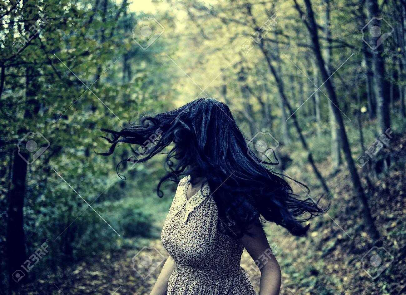 Scared jeune femme qui traverse une forêt la nuit, en regardant en arrière Banque d'images - 33375544