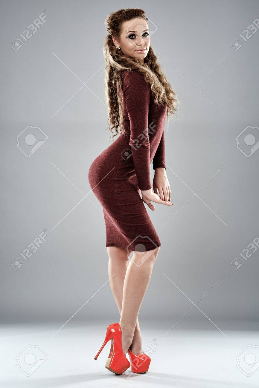 03385e9ccdb50 Gorgeous fashion model in tight dress and high heels posing on gray  background Stock Photo -