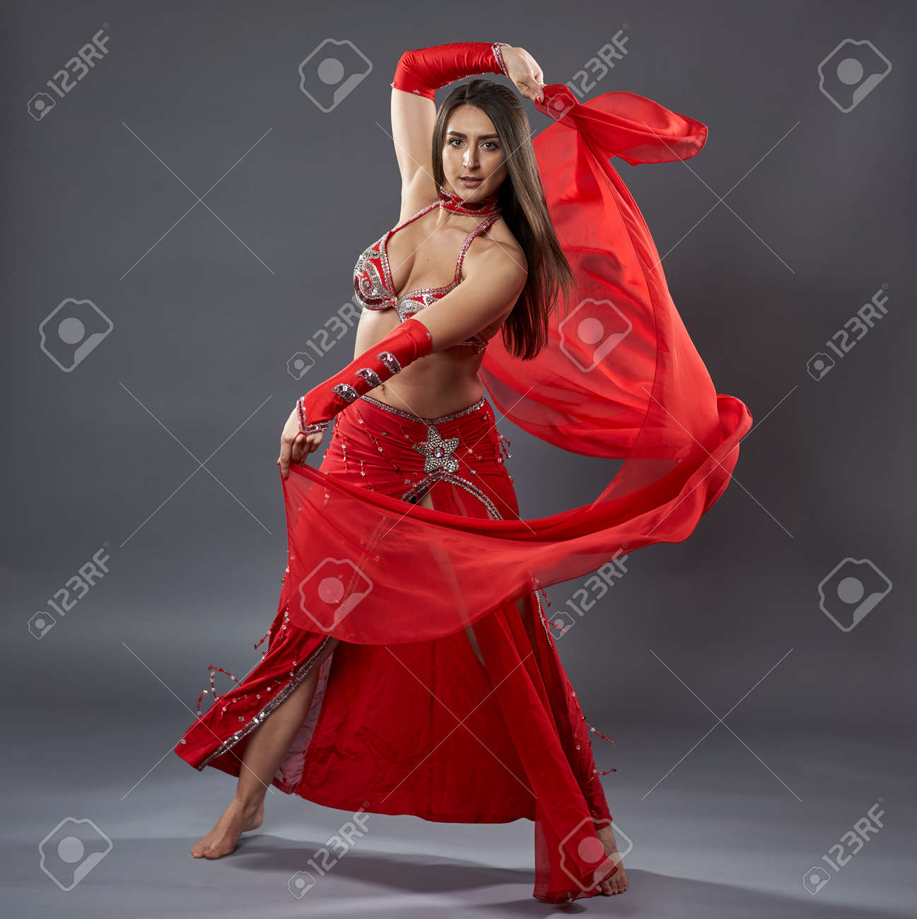 Arab woman belly dancer in red sparkling costume on gray background - 164412588