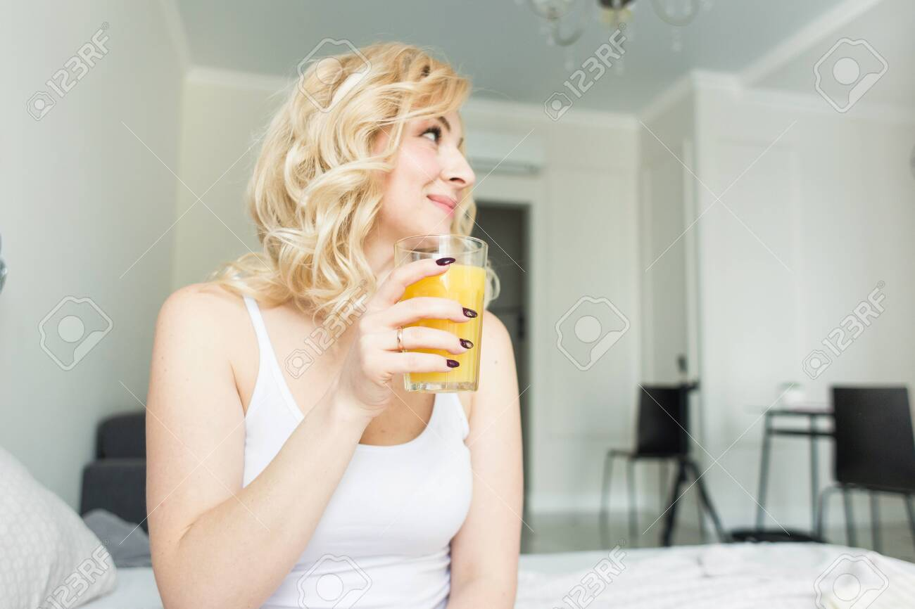 Attractive blonde woman sits on the edge of the bed at home and holds a stocker with orange juice in her hand. Morning mood and vigor - 122032214