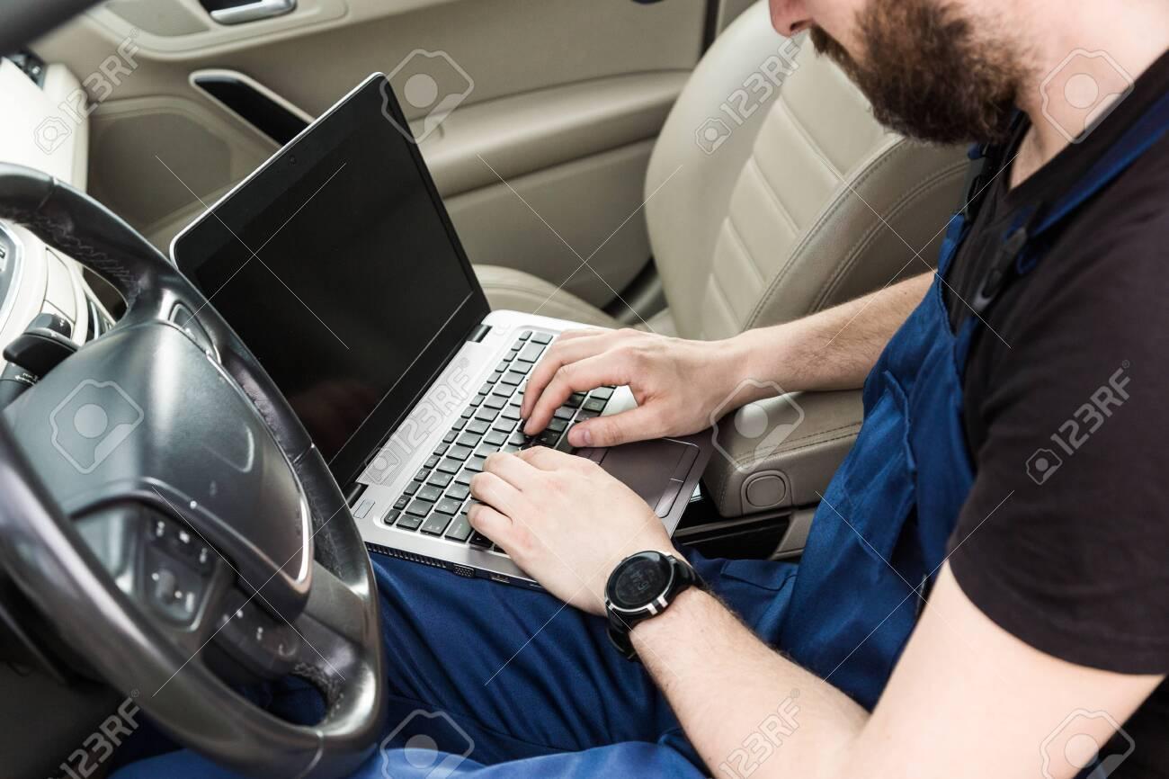 Professional car mechanic working in auto repair service. Computer video investigate. Engine diagnostics. Service station - 142320642