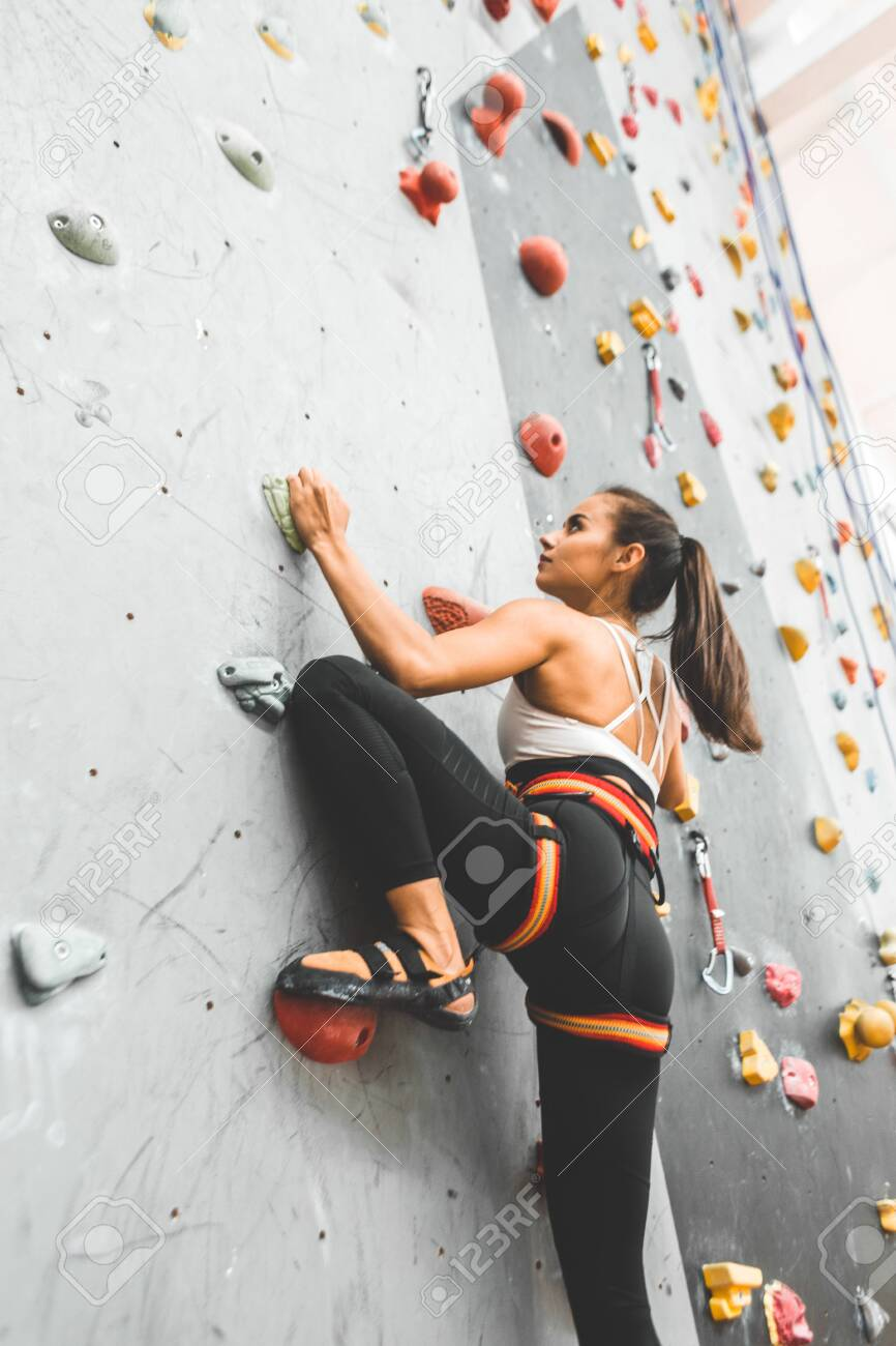 Sportswoman climber moving up on steep rock, climbing on artificial wall indoors. Extreme sports and bouldering concept - 150841561