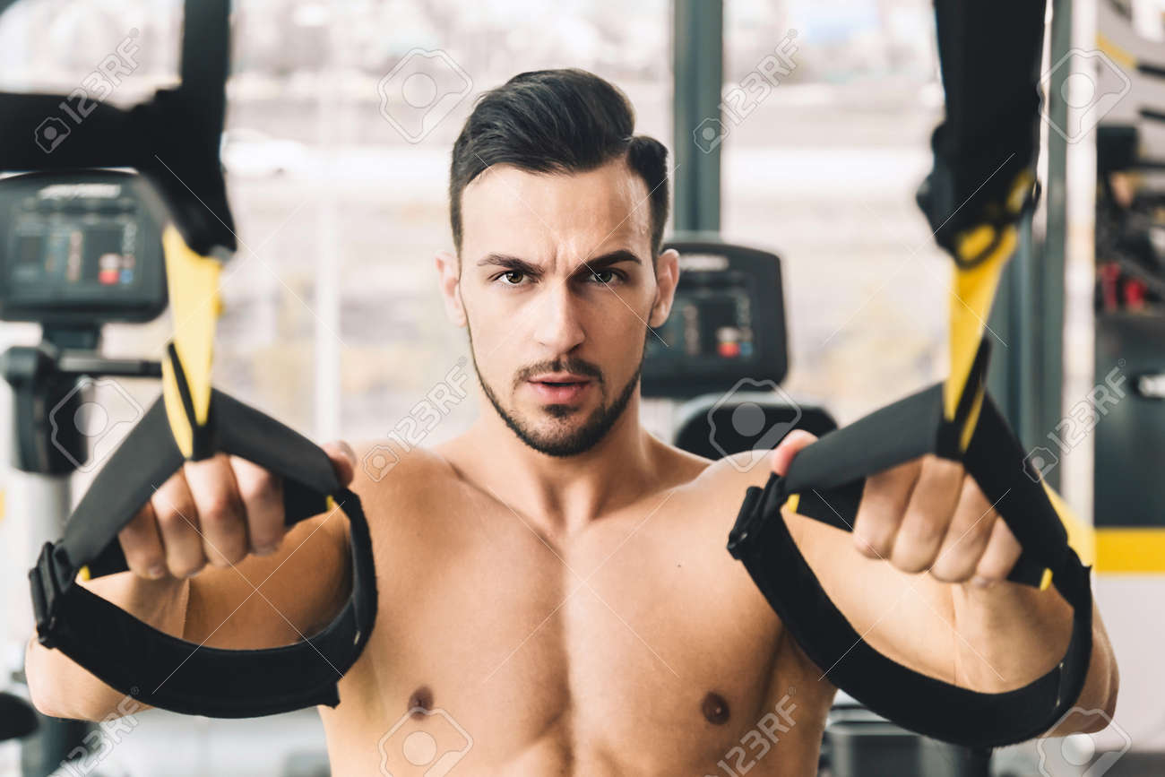 Handsome young sporty male bodybuilder with torso doing exercises in the gym - 171606167