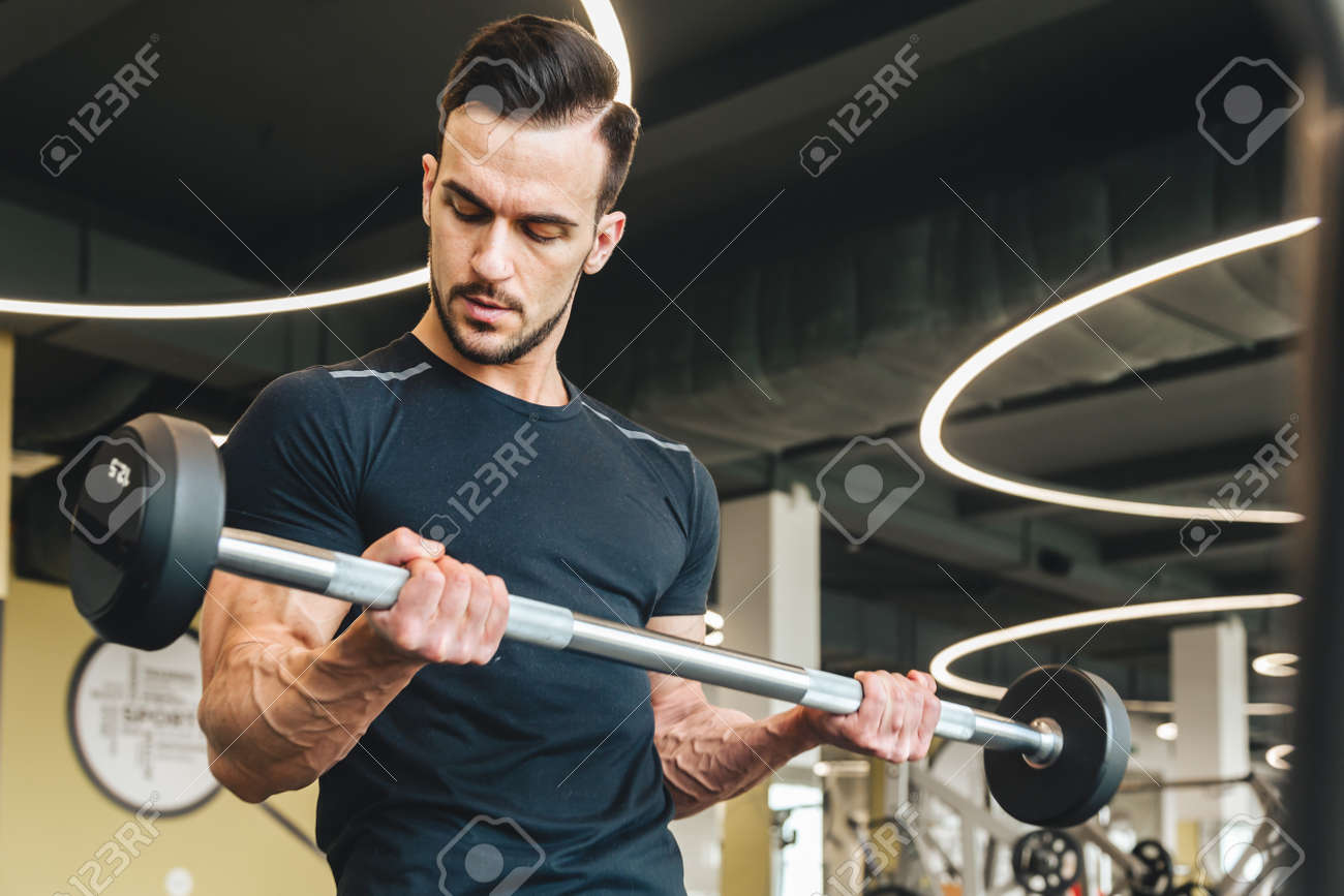 Handsome young sporty male bodybuilder doing barbell exercise in gym - 171606177
