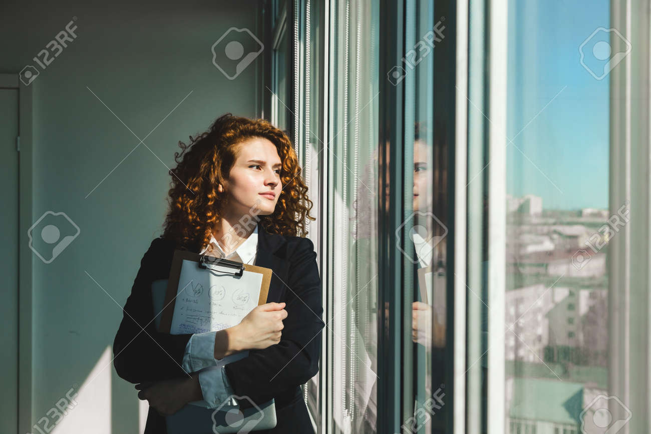 Portrait of a beautiful successful young business woman with red curly hair in the office interior stands near the window - 171606184