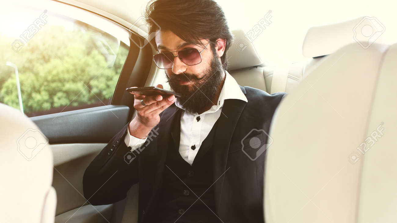 Stylish handsome Hindu businessman with glasses and a beard works in the backseat of the car and uses the phone. Safe and comfortable luxury travel - 171669295
