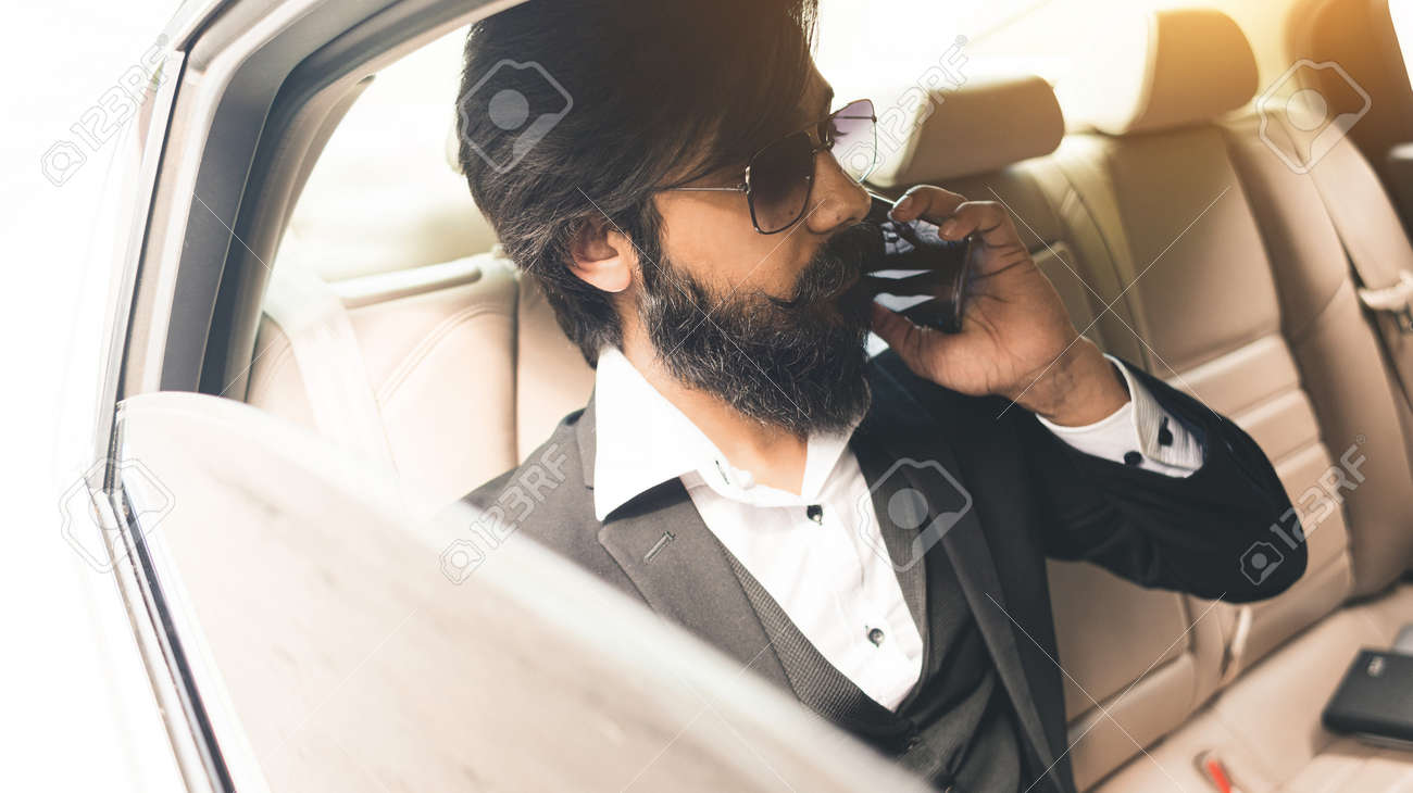 Stylish handsome Seo Hindu with glasses and a beard talking on the phone in the back seat of the car. Safe and comfortable business travel - 171668774