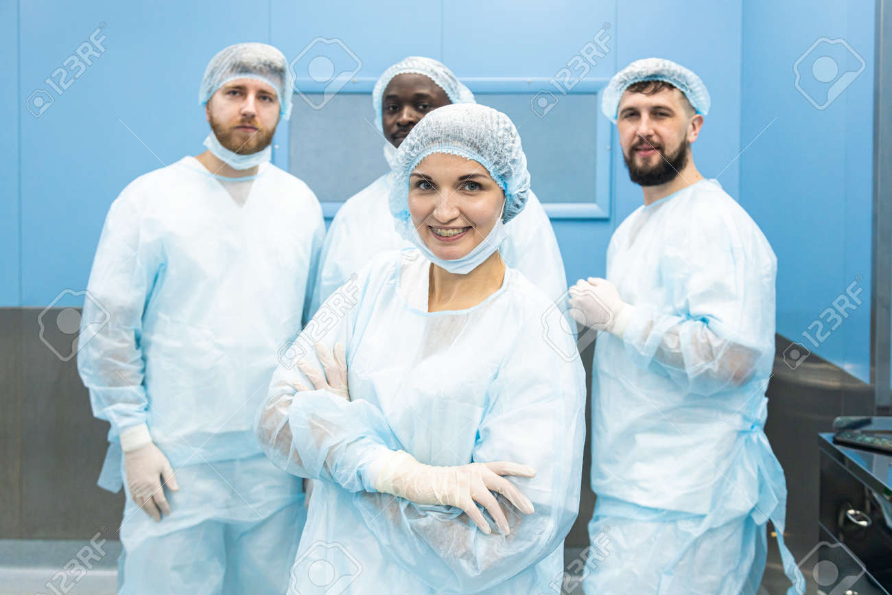 Portrait of a team of doctors in uniform and medical masks after completion of a surgical operation - 171614203
