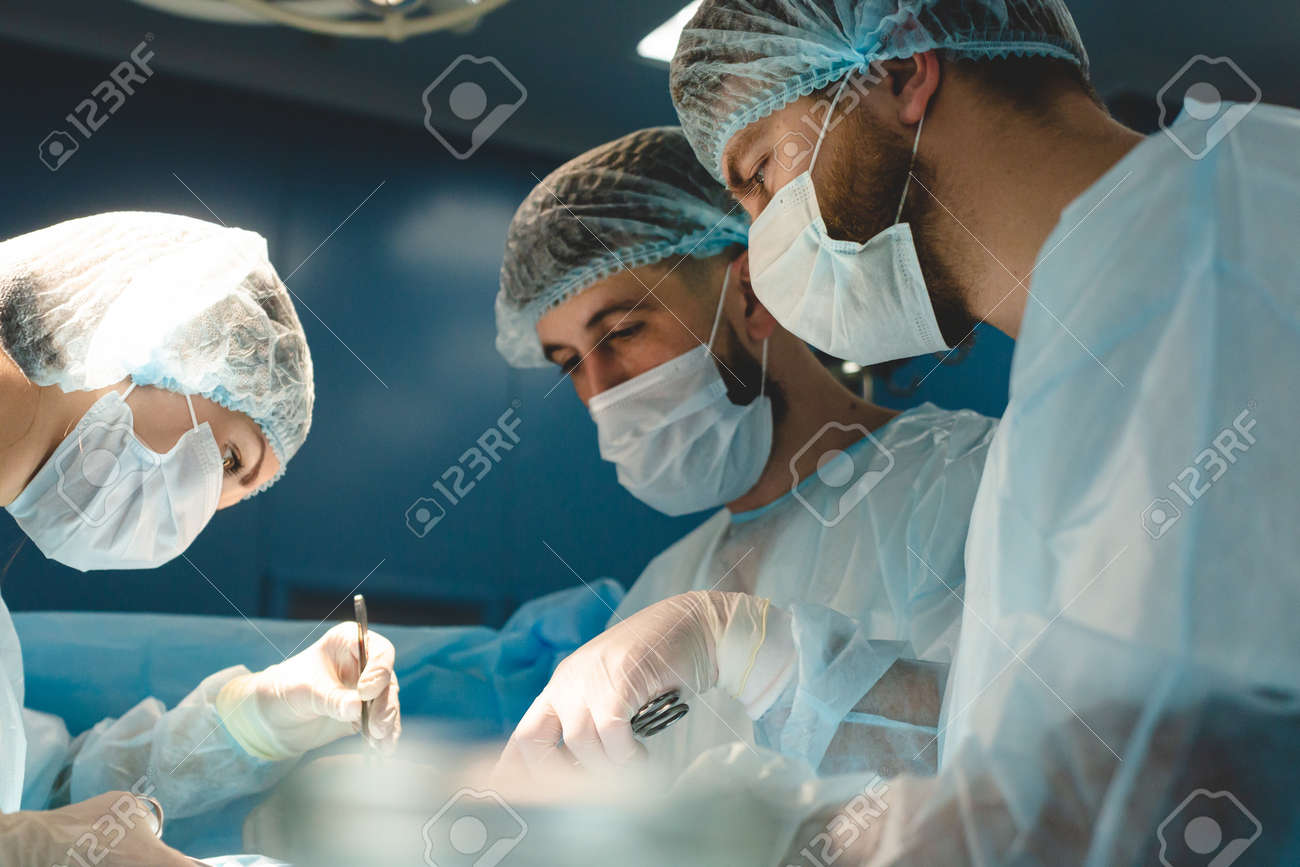 An international team of doctors performs a complex surgical operation on a patient under anesthesia. Modern operating room and experienced surgeons save lives - 171614704